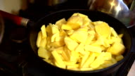 The glass lid puts the man's hand on a cast-iron frying pan with fried potatoes. video