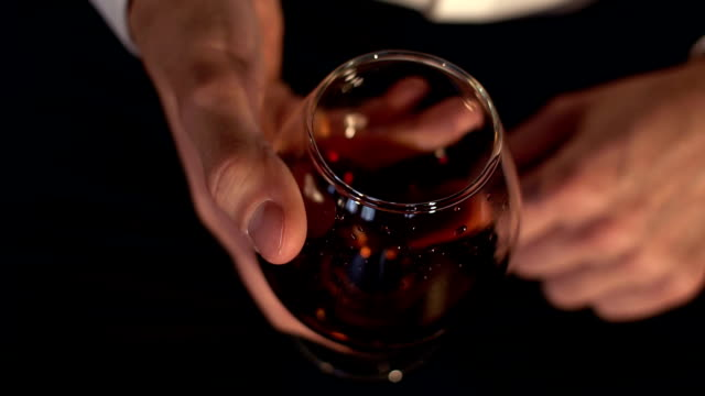 The glass with splashes cognac, slow motion. Glass of cognac in the man's hand. video