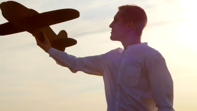 The guy at sunset dreams and plays with the airplane. video