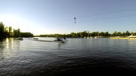 The guy doing tricks on a wakeboard in slow motion on the lake. video