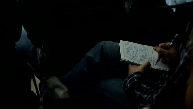 The guy in plaid shirt holding a notebook on his lap, and writes in it video