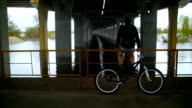 The Guy Is Resting Under A Bridge With A Bike video