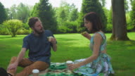 The guy with the girl eat salad sandwiches on picnic washed down with coffee. Communicate with each other video