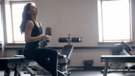 The gym on the edge of the bench sits a woman and dissolve hair video