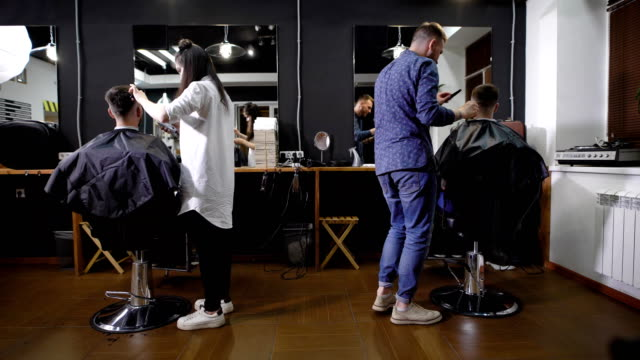 The hairdresser and his colleague cut hair for two men who came to the beauty salon for men, customers sit in armchairs and wait for the completion of their hairstyles video