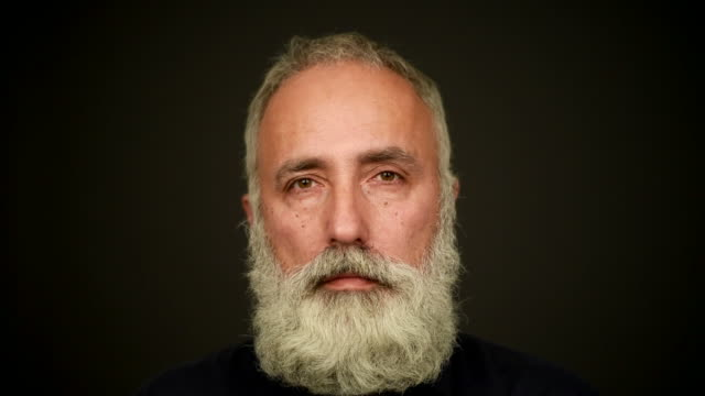 the head of an elderly gray-haired bearded man on a dark background. video