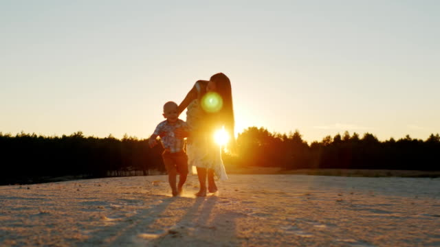 The little boy takes the first steps in the sunset, my mother supports him video
