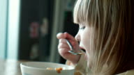 The little girl eats at a table video