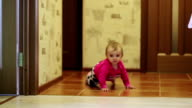 The little girl is crawling on the floor. video