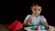 The little girl put colored eggs in the bag. video