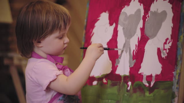 The little girl with short hair paint picture concentrated mouse video