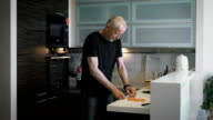 The man at the age of preparing a meal in their modern kitchen video
