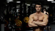 The man, athlete, personal trainer with steely glance and closed posture is standing in the gym video