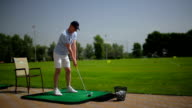 The man brandish a club and hits the ball video