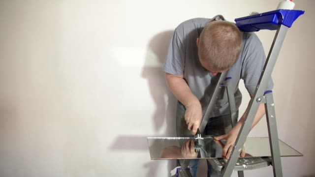 The man cuts the mirror with a glass cutter. video