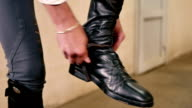 The man fasten a belt on the boots video