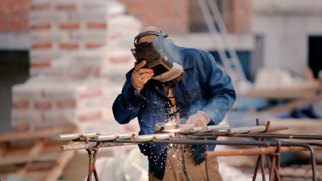 The man in helmet weld the pipe to construction video