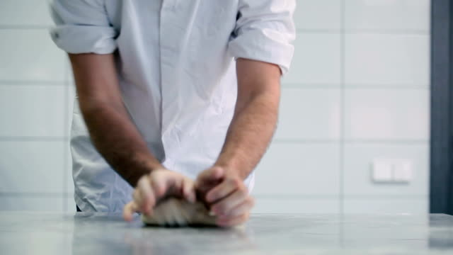 The man knead the dough at the table in the kitchen video