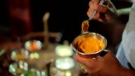 The man mix the spices in a bowl in the restaurant video