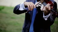 The man playing the violin. Outdoors video