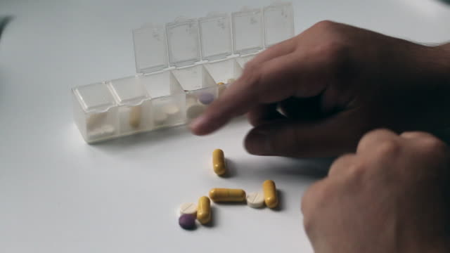 The man puts the tablets into a container. video
