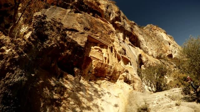 The Man Rocks figures in niches Adamkayalar Mersin province Turkey some trees around bottom view video