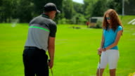 The man show the woman position in golf video