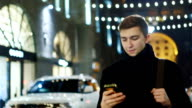 The man smiles, looks at his phone: sms reading, working with gadget video