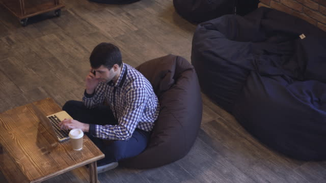The manager conducts telephone, looking at the computer that is on the table, standing next to a glass of coffee video