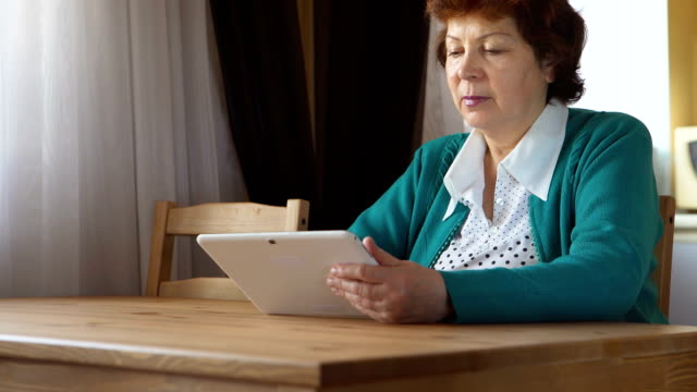 The mature woman is using a tablet PC at home video