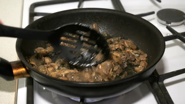 The mix of mushrooms is fried in a black pan video