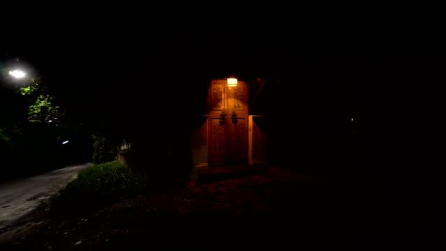 The old door is illuminated by a street lamp, next to the road. video
