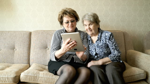 The old woman and her friend looking at pictures video
