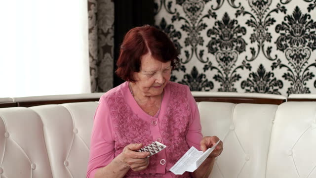 The old woman reads the instructions to pills. video