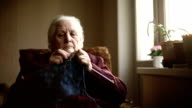 The old woman sits at home and knits garments video