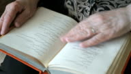 The old woman's hands holding and reading a book video