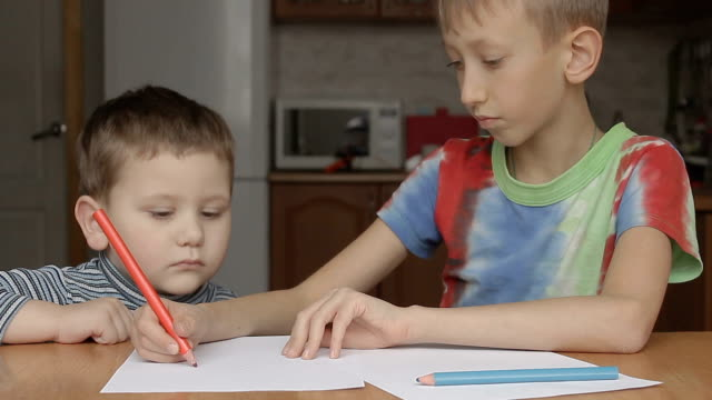 the older boy shows and says how to draw a crayon video