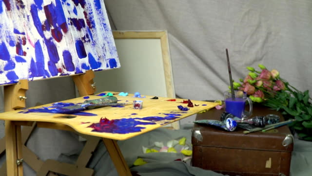 The painter's workplace, a wooden palette in oil paints, canvas, paints and brushes. There are flowers all around video