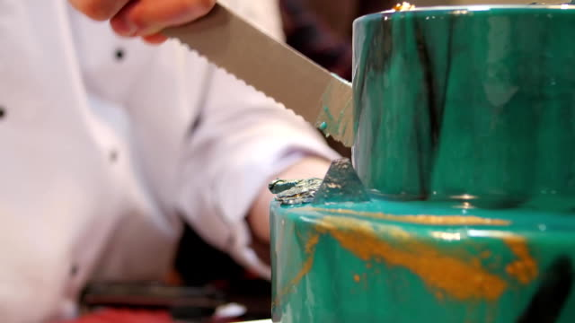 The pastry chef cut the cake with a long knife. Cut a turquoise cake. The pastry chef cut the cake video
