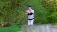 The performance of Wing Chun by man on forest background. Slowly video