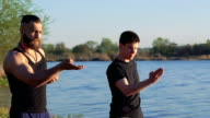 The performance of Wing Chun by strong men near river. Slowly video