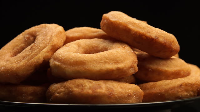 CLOSE UP: The pile of a doughnuts rotation on a black background video