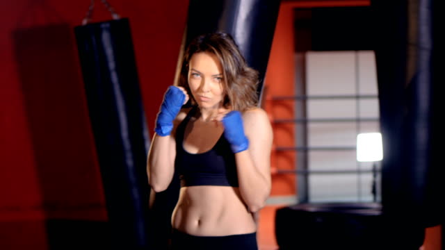 The portrait of the girl boxer demonstrating herself. 4K video