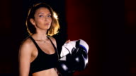 The portrait of the girl boxer with boxing gloves. 4K video