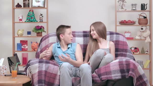 The relationships between teenagers resting in armchair indoors. video