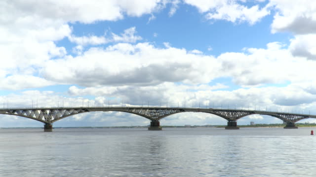 The road bridge across the Volga river between the cities of Saratov and Engels. Time lapse of river scenery. Floating across the sky. The movement of vehicles on the bridge. Summer day. Russia. video