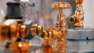 The rows of gilded parts of the water faucet on the shop showcase video