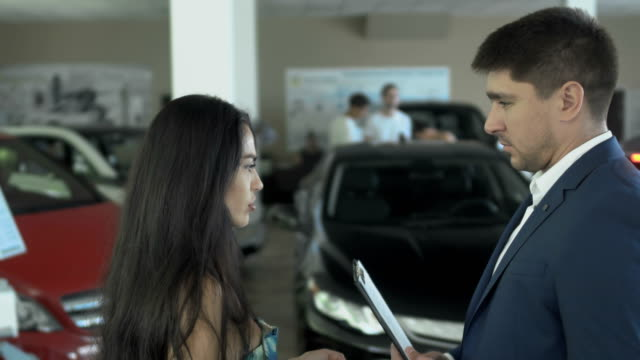 The salesman discuss the deal of buying a car with woman in car dealership video