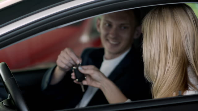The salesman gives a car keys to happy businesswoman in car dealership video