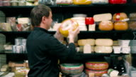 The salesman holding a piece of cheese in the supermarket video